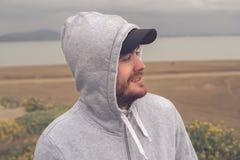 Junger Mann auf dem Strand, der einen Hoodie und eine Baseballmütze trägt Stockfotografie