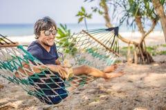 Junger Mann auf dem Strand in einer Hängematte mit einem Getränk stockfotografie