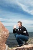 Junger Mann auf den Felsen auf dem Hintergrund von Meer Lizenzfreie Stockbilder