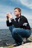 Junger Mann auf den Felsen auf Seehintergrund Stockfotos