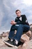 Junger Mann auf den Felsen in den Wolken Lizenzfreies Stockfoto