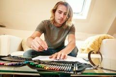 Junger Mann auf der Couch, zeichnend in Malbuch Stockbilder
