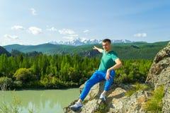 Junger Mann auf einem Felsen auf einem sonnigen warmen Herbstsommertagstillstehenden wh lizenzfreie stockfotos