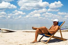Junger Mann auf einem Stuhl auf einem Strand Stockbild