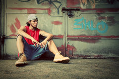 Junger Mann auf Graffiti grunge Wand Stockfotografie