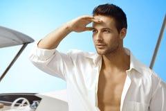 Junger Mann auf Segelboot an der Sommerzeit Stockfoto