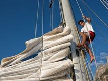 Junger Mann auf Segelschiff, aktiver Lebensstil, Sommersportkonzept Lizenzfreie Stockfotos