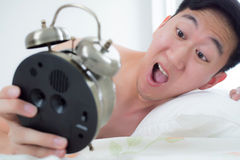 Junger Mann auf seinem Kopfende, wissend, dass er und spät für seinen Zeitplan verschlief lizenzfreie stockfotografie