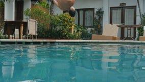 Junger Mann auf springendem leichtem Schlag der Sommerferien in blaues Poolwasser für Erfrischung am heißen sonnigen Tag Kerltauc stock video footage