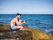 Junger Mann auf Strandlesung mit ebook Leser stockfotos