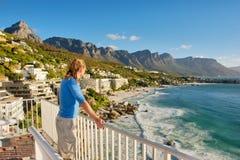 Junger Mann auf Terrasse betrachtet Strandpanorama stockbilder