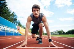 Junger Mann in Ausgangsposition für das Laufen auf Sportbahn Stockbild