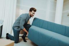 Junger Mann befördert großen Sofa In The New Apartment lizenzfreie stockfotos