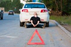 Junger Mann benennt zu einem Service standi durch ein weißes Auto Stockfoto