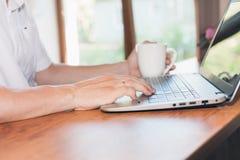 Junger Mann benutzt Laptop und trinkender Kaffee oder Tee an seinem Arbeitsplatz Stockfotografie