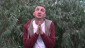 Junger Mann betet mit Gesicht voll von Lippenstiftkennzeichen von Küssen stock video