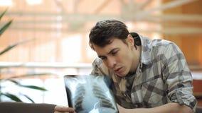 Junger Mann betrachtet aufmerksam Röntgenaufnahme von Lungen stock video
