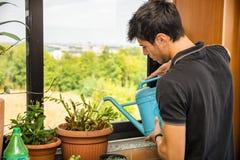 Junger Mann-Bewässerungs-Anlagen auf Wohnungs-Balkon Stockbilder