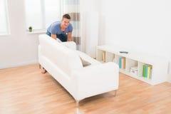 Junger Mann-bewegliches Sofa Lizenzfreie Stockfotos