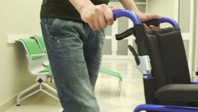 Junger Mann bewegt Rollstuhl in der Voraussetzung im Krankenhaus stock footage