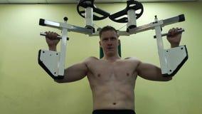 Junger Mann bildet Brustmuskeln in der Turnhalle aus und tut Eignung stock video