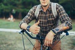 Junger Mann bildet Daumen durch die Hände, die auf einem Fahrrad auf grüner Sommer-Wiese sitzen Stockfoto