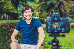 Junger Mann Blogger notiert Video vor der Kamera im Park Lizenzfreies Stockfoto