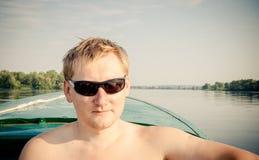 Junger Mann an Bord des Bootes Weitwinkelfoto genommen: Frühling 2009 Lizenzfreie Stockfotos