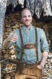 Junger Mann in den bayerischen Lederhosen mit den Daumen oben Lizenzfreie Stockfotos
