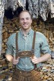 Junger Mann in den bayerischen Lederhosen vor Brennholz Lizenzfreies Stockfoto