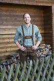Junger Mann in den bayerischen Lederhosen vor Brennholz Stockbild