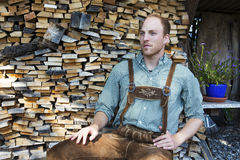 Junger Mann in den bayerischen Lederhosen vor Brennholz Stockbilder