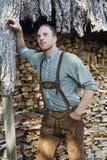 Junger Mann in den bayerischen Lederhosen vor Brennholz Stockfotografie