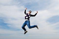 Junger Mann in den Brillen, die in Wolken springen Lizenzfreie Stockfotos