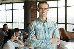 Junger Mann in den Brillen lächelnd an der Kamera am Treffen stockfoto