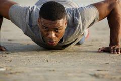 Junger Mann, den das Handeln drückt, ups draußen Stockfotografie