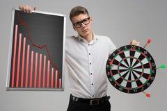 Junger Mann in den Gläsern, die ein Brett mit fallenden Statistiken und die Pfeile lokalisiert auf weißem Hintergrund halten lizenzfreie stockfotos