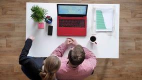 Junger Mann in den Gläsern, die Frau einladen, mit jemand durch Laptop, topshot, Schreibtisch mit Kaffee und Dokumente zu spreche stock footage