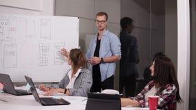Junger Mann in den Gläsern, die seine Ansichten mit Mitarbeitern im Sitzungssaal während des Geschäftstreffens teilen Team von de stock video footage