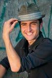 Junger Mann in den Grüßen eines Hutes stockfotos