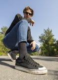 Junger Mann in den Jeans und in den Turnschuhen sitzt auf der Straße im Wald lizenzfreie stockbilder