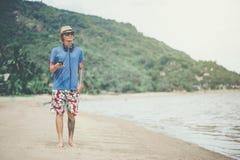 Junger Mann in den Kopfhörern und in der Sonnenbrille am Strand hörend Musik stockfoto