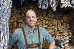 Junger Mann in den Lederhosen vor Brennholz Stockbilder