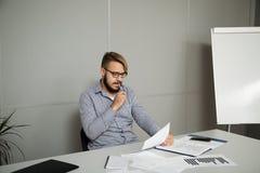 Junger Mann denkt auf einem neuen Vertrag Stockfotos