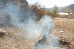 Junger Mann, der über einem rauchenden Feuer kocht Stockfotos