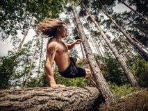 Junger Mann, der über einen Baumstamm im Wald springt stockfoto