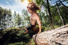 Junger Mann, der über einen Baumstamm im Wald springt lizenzfreie stockbilder