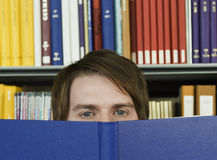 Junger Mann, der über geöffnetes Buch späht Stockbild