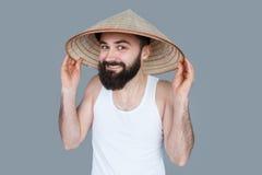 Junger Mann, der über grauem Hintergrund lächelt Lizenzfreies Stockbild