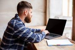 Junger Mann, der über Netzbuch während des Arbeitsbruches in der Kaffeestube, Mann sitzt in der offenen Laptop-Computer der Front Lizenzfreies Stockbild